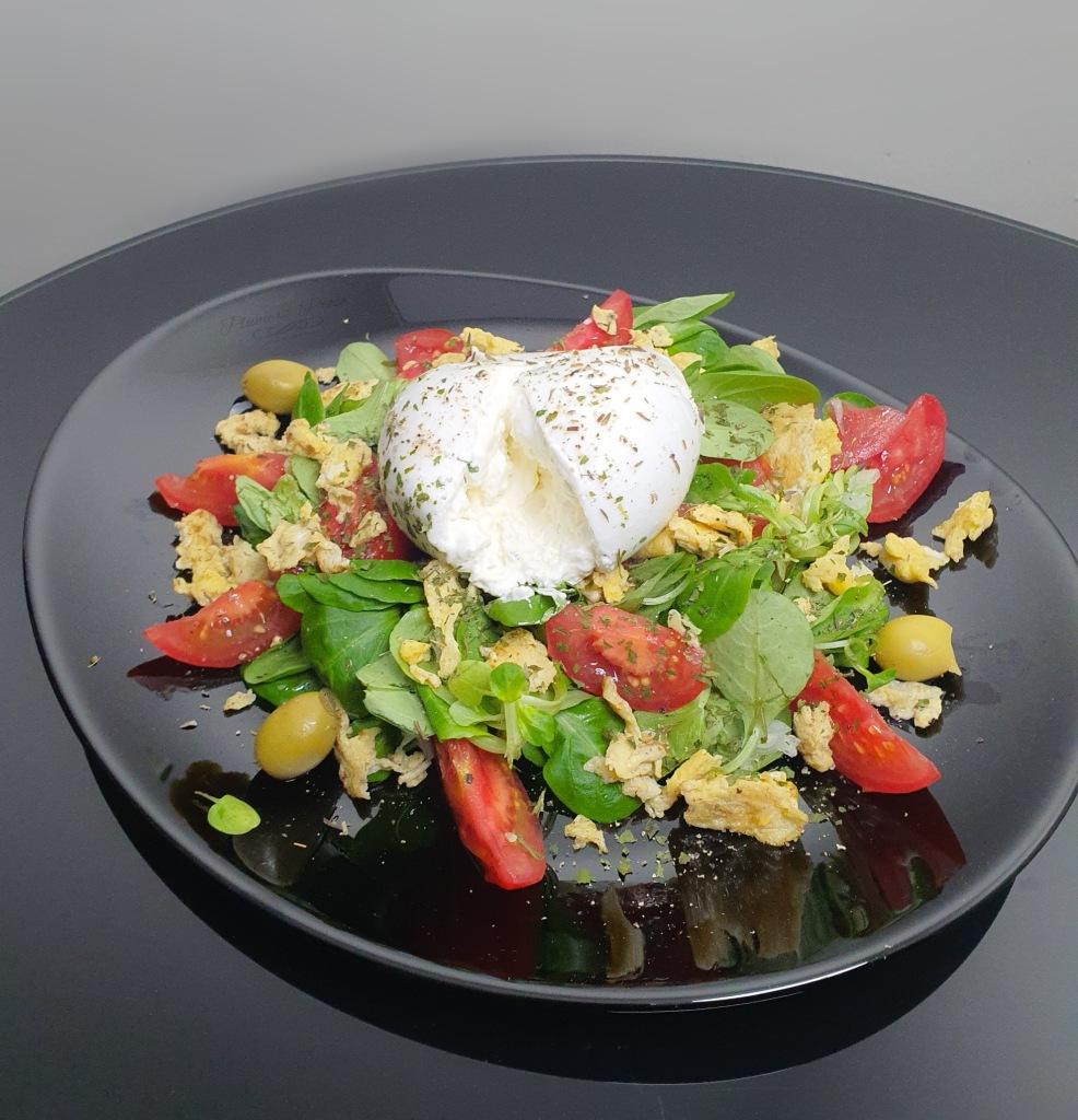 Salade de tomates et burrata sur son lit de mâche et oeufs brouillés